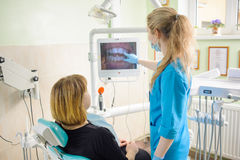 female dentist showing photograph of teeth on computer to patient Stock Photography