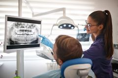 Dentist showing x-ray footage of teeth to patient Stock Photos