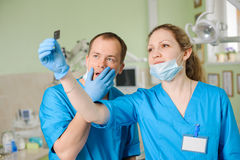 Female dentist showing x-ray to male colleague at dental clinic Royalty Free Stock Photography