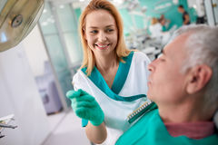 Female dentist shows to patient closest color of teeth for dentu Royalty Free Stock Photography