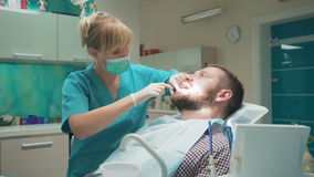 Female dentist sits down and examining teeth of male patient. Slider shot stock video footage