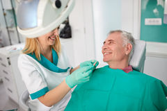 Female dentist strives to find closest color of dentures teeth Stock Photos