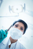 Female dentist in surgical mask holding dental drill Stock Image