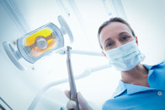 Female dentist in surgical mask holding dental tool Stock Photo