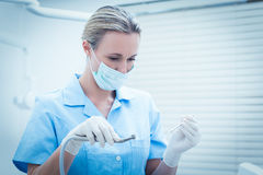 Female dentist in surgical mask holding dental tools Royalty Free Stock Photography