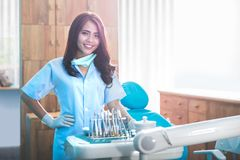 Female dentist with tools over medical office clinic. Happy young female dentist with tools over medical office clinic Stock Photo