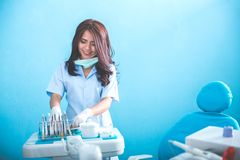 Female dentist with tools over medical office clinic. Happy young female dentist with tools over medical office clinic Stock Photography