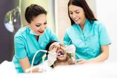 Female dentist treating male patient in dentist`s chair, using dental drill. Royalty Free Stock Photo