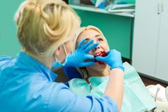 Female dentist treating patient girl teeth. Young blonde girl sitting at the dentist.  royalty free stock photography