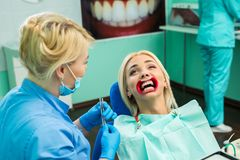 Female dentist treating patient girl teeth. Young blonde girl sitting at the dentist.  stock photo