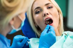 Female dentist treating patient girl teeth. Young blonde girl sitting at the dentist.  stock photography