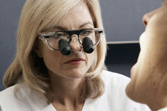 Female dentist wearing surgical loupes, examining patient, close-up Stock Photo