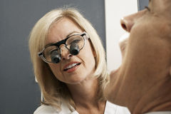 Female dentist wearing surgical loupes, examining patient, close-up (differential focus) Stock Photos