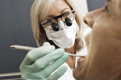 Female dentist wearing surgical loupes and mask, examining patient, using dental tool, close-up Stock Image