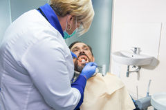 Female dentist at work. Doctor checking teeth of patient Royalty Free Stock Photo
