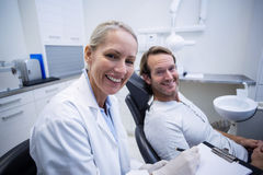 Female dentist writing on clipboard while interacting with male patient Royalty Free Stock Photography