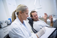 Female dentist writing on clipboard while interacting with male patient Stock Photography