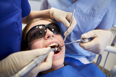 Female dentists treating patient girl teeth Stock Photography