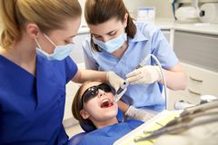 Female dentists treating patient girl teeth Royalty Free Stock Images