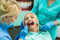 Female dentists treating patient girl teeth. Young blonde girl sittiong at the dentist.  stock photography