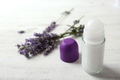 Female deodorant and lavender flowers on white table. Space for text