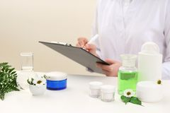 Female dermatologist doing research for new skin care product at table. Closeup stock photos