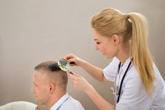 Female Dermatologist Looking Hair Through Magnifying Glass Royalty Free Stock Photography