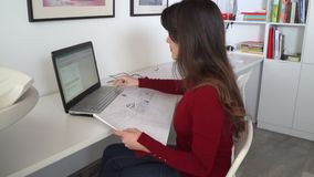 Design engineer sits at the desk in her office, types on a laptop, blueprints laying on her desk