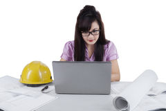 Female designer with blueprint and laptop Stock Photos