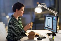 Female designer eating and working at night office. Business, deadline and people concept - female graphic designer eating takeaway wok food by chopsticks and stock image