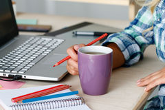 Female designer hands holding cup of hot beverage and drawing wi Royalty Free Stock Image