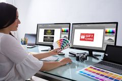 Female Designer Holding Color Swatch Working In Office. Female Designer Holding Color Swatch Working With Gift Card On Computer Screen stock images