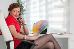 Female designer of interior. Young female designer of interior sits on the workplace at the office royalty free stock photography