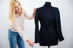 Female designer measuring jacket Stock Images