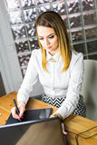 Female designer in office working with digital graphic tablet and laptop. Photography retoucher sitting at desk Royalty Free Stock Images