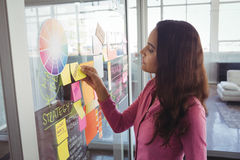 Female designer removing adhesive note from glass in creative office Stock Image