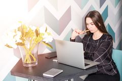 Female designer thinking about new ideas using net-book during rest in coffee shop.Girl booking. Young thoughtful woman university student learning online via Stock Images