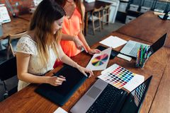 Female designer working with client at desk in her office.  stock photo