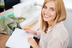 Female designer writing notes in workshop Royalty Free Stock Images