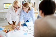 Female Designers Collaborating. Portrait of three successful businesswomen discussing lettering and fonts while collaborating on design project in studio royalty free stock photo