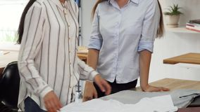 Female designers working at the clothing boutique. Cropped sliding shot of two female designers working at the clothing boutique. Shop assistant folding a t stock footage