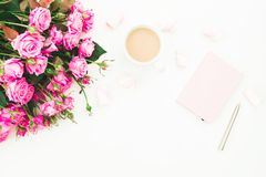 Female desk with bouquet of pink flowers, pink diary, coffee mug and marshmallows on white background. Flat lay. Top view feminine Royalty Free Stock Images