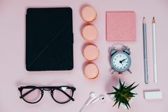 Female Desk on pink glasses notepad kicking pencils plant macaro. Ons alarm clock Top View Space For Text royalty free stock photos