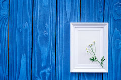 female desktop decoration with flowers and frame on blue wooden background top view mock-up Stock Photos