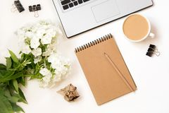 Female desktop with a laptop and white flowers on white background.Top view composition with copy space. Female desktop with a laptop, sketch-book,coffee and Stock Photos