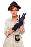 Female Detective with Badge Putting on Gloves. Red Haired Female Detective Putting on Gloves Wearing a Badge, Trenchcoat and Hat Isolated on a White Background Stock Images