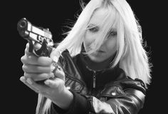 Female detective shooting with gun on the street at night Stock Photo