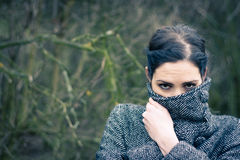 Female detective. Young woman mysteriously wrapping up in her coat royalty free stock photo