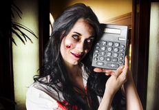 Female devil business woman showing profits. Concept image of a female devil business woman in terrifying makeup holding a calculator to portraying negetive cash Royalty Free Stock Photo