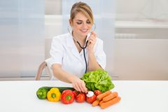 Female dietician examining vegetables Royalty Free Stock Photography